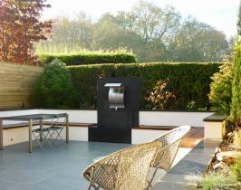 Small paved modern garden with storage hidden under benches