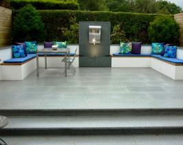 full width granite steps lead up to paved terrace and water feature with iron benches hiding storage