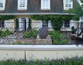 Contemporary garden design behind bespoke railings and gates