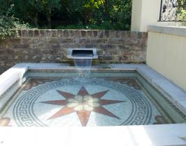 Shallow garden water feature with bespoke mosaic pattern to pool base