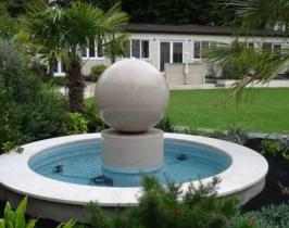 Garden water feature using limestone sphere on circular base and limestone copings